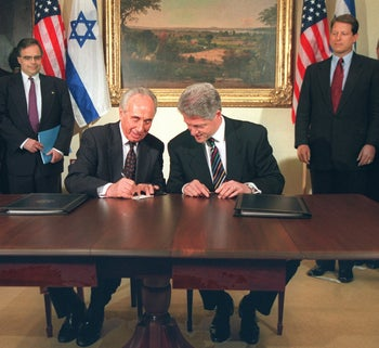 Israeli Prime Minister Shimon Peres writes U.S. President Bill Clinton's name in Hebrew after they sign a joint declaration on terrorism, April 30, 1996, less than a month before Israeli elections