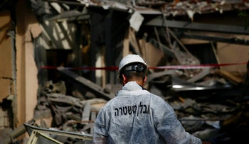 A police officer inspects the damage to a house hit by a rocket in Mishmeret, central Israel, March 25, 2019.