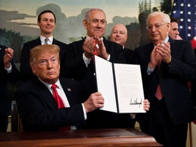 President Donald Trump holds up a signed proclamation recognizing Israel's sovereignty over the Golan Heights, as Israeli Prime Minister Benjamin Netanyahu looks on, Washington, D.C., March 25, 2019.
