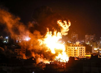 Fire and smoke below above buildings in Gaza City during reported Israeli strikes on March 25, 2019