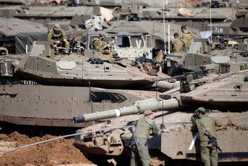 Israeli soldiers work on their tanks at a gathering area near the Israel-Gaza border, in southern Israel, on Tuesday, March 26, 2019.