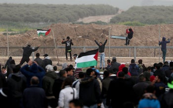 Palestinian demonstrators climb over Israeli border fence during a protest east of Gaza City February 15, 2019.