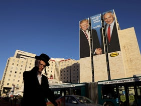 A man walks past a Likud election campaign billboard, depicting U.S. President Donald Trump shaking hands with Israeli Prime Minister Benjamin Netanyahu, in Jerusalem February 4, 2019.