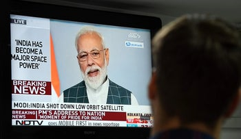A man watches Indian Prime Minister Narendra Modi's address to the nation on a local news channel in New Delhi on March 27, 2019.