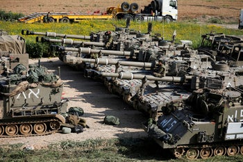 Israeli soldiers are seen next to mobile artillery units near the border with Gaza, southern Israel, March 27, 2019.