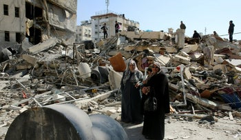 Palestinians search for their family's belongings amid the rubble of destroyed building near a Hamas security building that was destroyed in an Israeli airstrike, in Gaza City, March 27, 2019.