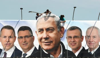 Labourers hanging up a Likud election campaign banner depicting Prime Minister Benjamin Netanyahu with his party candidates, Jerusalem, March 28, 2019.