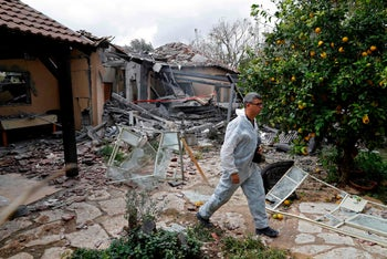 An emergency responder inspecting a damaged house after it was hit by a rocket in the village of Mishmeret, north of Tel Aviv on March 25, 2019
