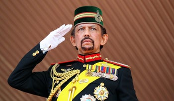 Brunei's Sultan Hassanal Bolkiah salutes during a ceremonial guard of honour to mark his 68th birthday celebrations in Bandar Seri Begawan on August 14, 2014.