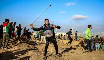 File photo: A Palestinian protester uses a slingshot to hurl objects during clashes with Israeli forces across the fence following a demonstration east of Gaza City, March 22, 2019.