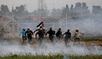 Palestinian demonstrators run away from Israeli fire and tear gas during a protest at the Israel-Gaza border fence, in the southern Gaza Strip, February 15, 2019.