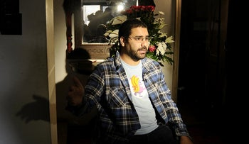 Egyptian blogger and activist Alaa Abdel-Fattah speaks during a TV interview at his house in Cairo on December 26, 2011.