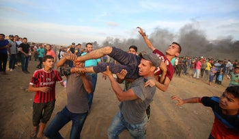FILE PHOTO: Palestinian paramedics carry a wounded protester during clashes with Israeli forces east of Gaza city, October 5, 2018.