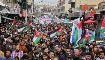 Protesters from the Islamic Action Front and others march with Jordanian flags and other banners as they chant slogans during a protest marking the Land Day in the Jordanian capital Amman, March 29, 2019.