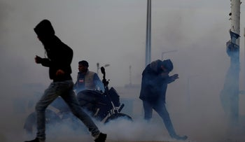Palestinians react to tear gas fired by Israeli troops during a protest at the Israeli-Gaza border fence, March 29, 2019.