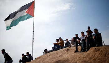 Palestinian sit near to the Israeli-Gaza border fence, ahead of the first anniversary of border protests, east of Gaza City, March 29, 2019.