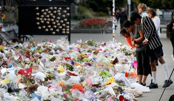 People look at the flowers and tributes displayed in memory of the twin mosque massacre victims at the Botanical Garden in Christchurch, March 29, 2019.