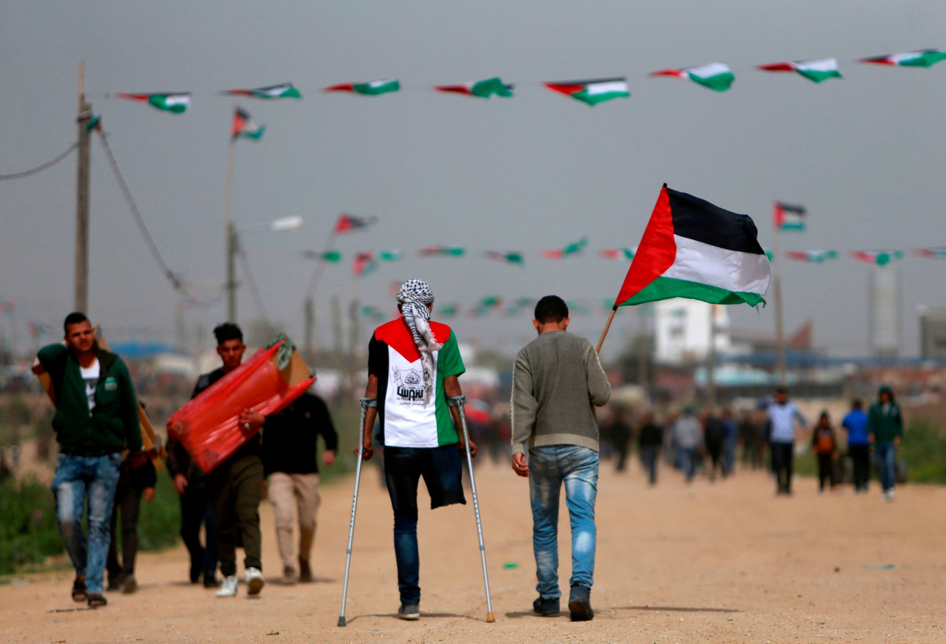 A Palestinian amputee walks on crutches with another holding a Palestinian flag as they head toward a demonstration near the border with Israel, east of Gaza City, March 30, 2019.
