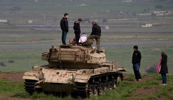 Israelis stand on a defunct tank in the Golan Heights, March 2019.