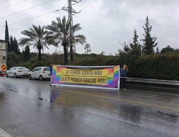 "LGBT activists holding up a sign in Portuguese that reads ""The Holy Land doesn't want homophobes here"" near the exit from Ben-Gurion International Airport, March 31, 2019"