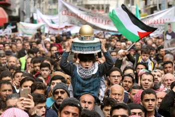 A boy holds a model depicting the Dome of the Rock during a protest marking the Land Day in Amman, Jordan, March 29, 2019