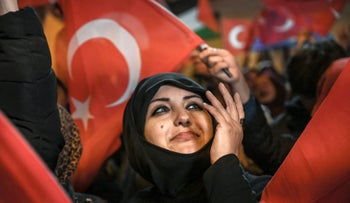 A supporter of AK Party looks on as she waves a Turkish national flag during a rally near the party headquarters in Istanbul, March 31, 2019.