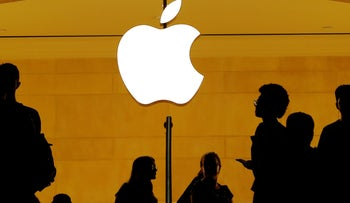 File photo: Customers walk past an Apple logo inside of an Apple store at Grand Central Station in New York, U.S., August 1, 2018.