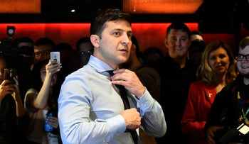 Volodymyr Zelensky surrounded by cameramen and photographers adjusts his tie as he plays table tennis with a journalist in Kiev on March 31, 2019.