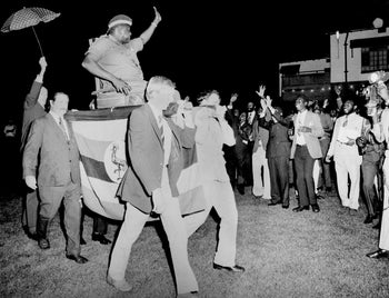 Ugandan President Idi Amin is carried in a chair by four British businessmen during a party for diplomats in this July 1975 file photo in Kampala, Uganda