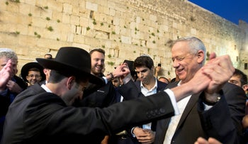 Benny Gantz, head of the Kahol Lavan party, dances with ultra-Orthodox Jewish men during his visit to the Western Wall, March 28, 2019.