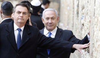 Brazilian President Jair Bolsonaro, accompanied by Prime Minister Benjamin Netanyahu, pose for a photo as they visit the Western Wall in Jerusalem's Old City, April 1, 2019.