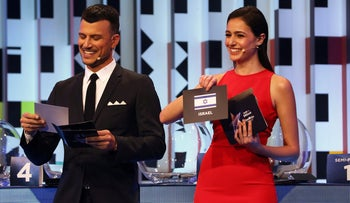 Television presenter Assi Azar stands next to Lucy Ayoub as she shows the card of Israel during the Eurovision Semi-Final allocation draw, in the Tel Aviv Museum of Art, Israel January 28, 2019.