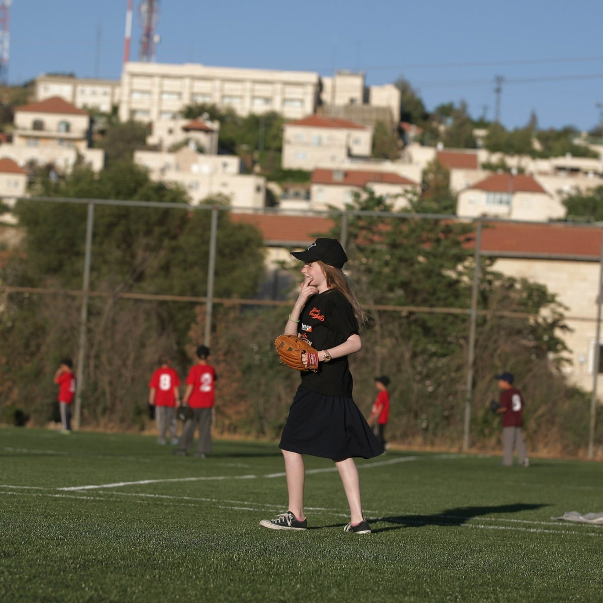 A young girl playing baseball in the West Bank settlement of Efrat.