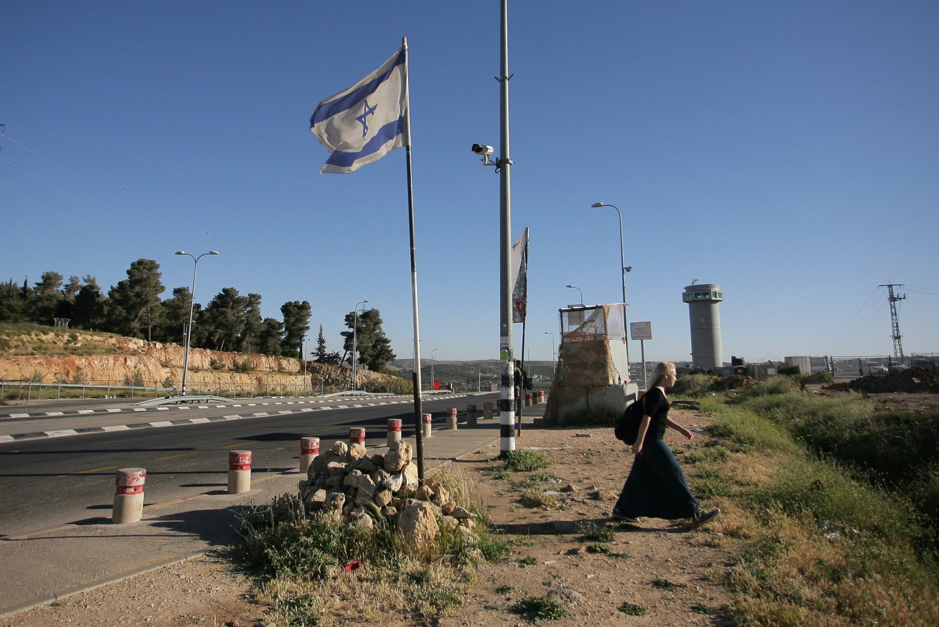 Heading rightward? A woman walking at the Efrat junction in the West Bank.