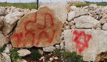 Spray-painted messages are seen at the site of a suspected hate crime in the Palestinian village of Deir Jarir, the West Bank, April 3, 2019.