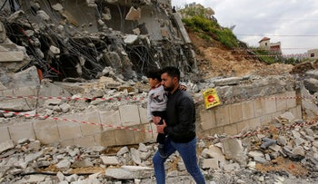 A man carrying a boy walks past the remains of a Palestinian house in Beit Jala, West Bank, April 2, 2019.
