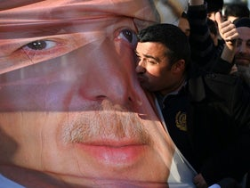 Erdogan supporters kiss a banner with his image on it outside the ruling AKP party headquarters in Istanbul a day after local elections. April 1, 2019