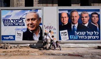 People walking by election campaign billboards in Tel Aviv for Likud and Kahol Lavan, April 3, 2019.