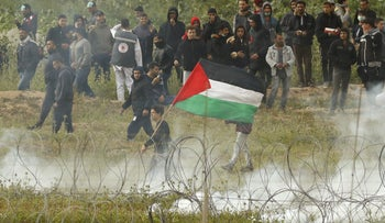 Palestinian protesters are seen demonstrating on the Gazan side of the border to mark the first anniversary of the 'March of Return' protests, Nahal Oz, Israel, March 30, 2019.