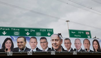 A man works on a Likud party election campaign billboard depicting Prime Minister Benjamin Netanyahu and his party candidates, Petah Tikva, Israel, April 1, 2019.