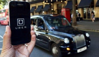 FILE PHOTO: A photo illustration shows the Uber app logo displayed on a mobile phone in central London, Britain August 17, 2016.
