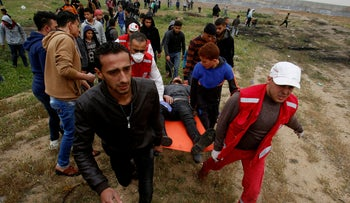 Medics and protester evacuate a wounded youth, who was shot by Israeli troops while marking the first anniversary of Gaza border protests, March 30, 2019.