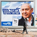 A man walks past electoral campaign posters in Tel Aviv on April 3, 2019.