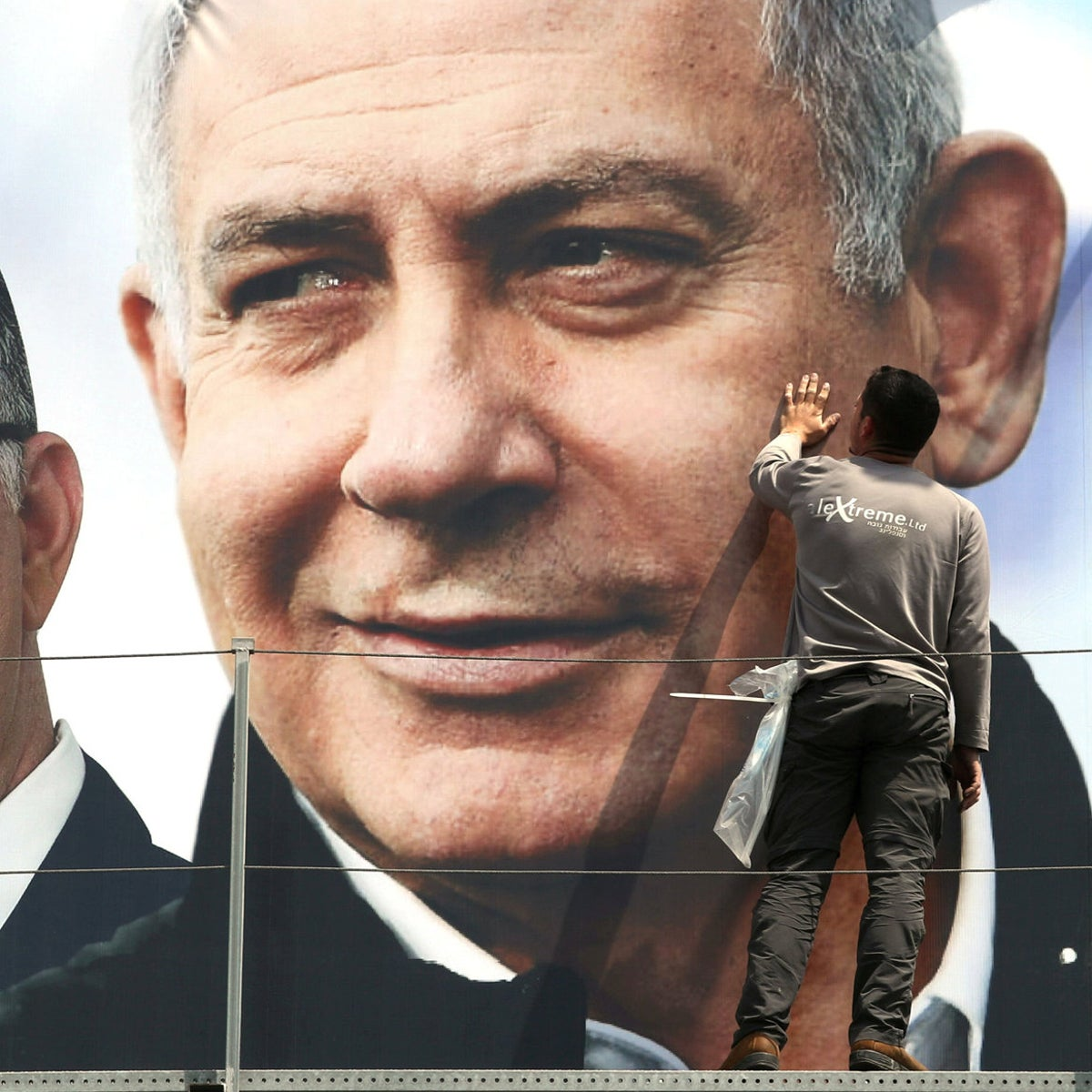 A labourer works on hanging up a Likud election campaign banner depicting Israeli Prime Minister Benjamin Netanyahu with his party candidates, in Jerusalem. March 28, 2019