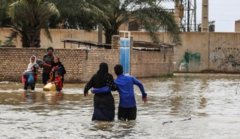 An Iranian family walks through a flooded street in a village around the city of Ahvaz, in Iran's Khuzestan province, March 31, 2019.