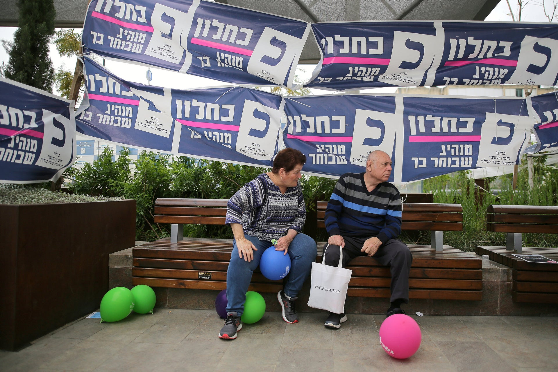 Shoppers resting at a mall in Rehovot with ads for Moshe Kahlon's Kulanu party behind them, April 4, 2019.
