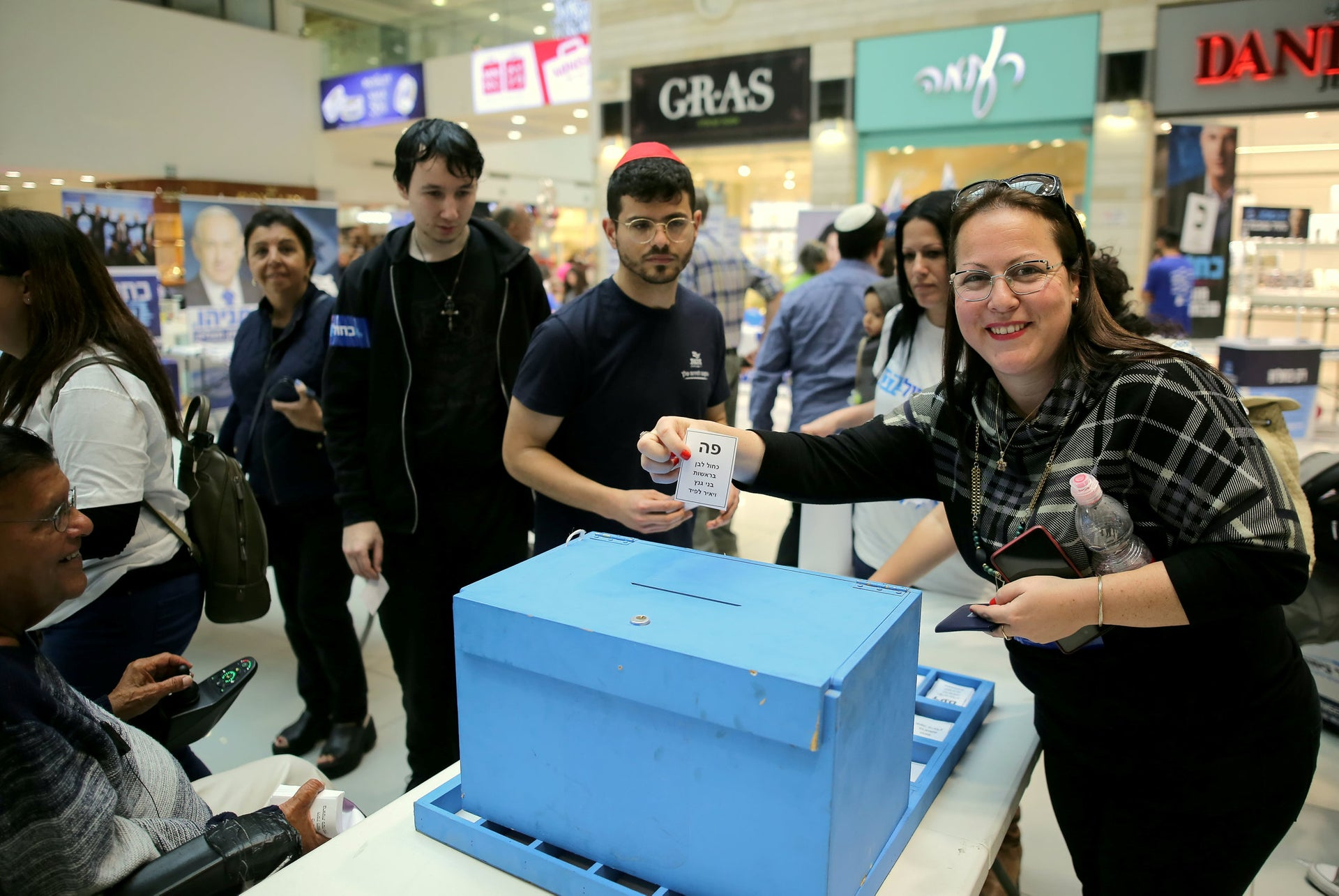 A voter casting her ballot for Kahol Lavan into a fake election box in a Rehovot mall, April 4, 2019.