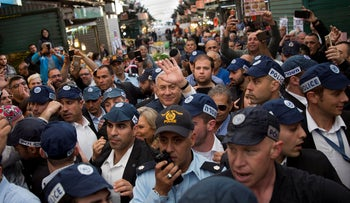 Israeli Prime Minister and head of the Likud party Benjamin Netanyahu, center, is escorted by security guards during a visit to the Ha'tikva market in Tel Aviv. April 2, 2019