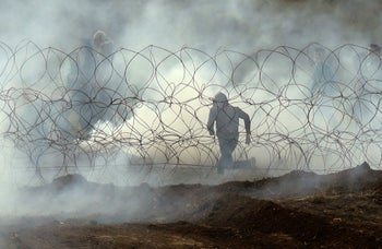 "A Palestinian protester running away from the border fence with Israel as Palestinians mark the first anniversary of the ""March of Return"" protests. March 30, 2019"