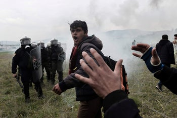 Migrants shout slogans during clashes with Greek riot police outside of a refugee camp in Diavata, a west suburb of Thessaloniki, where migrants gather on April 6, 2019.
